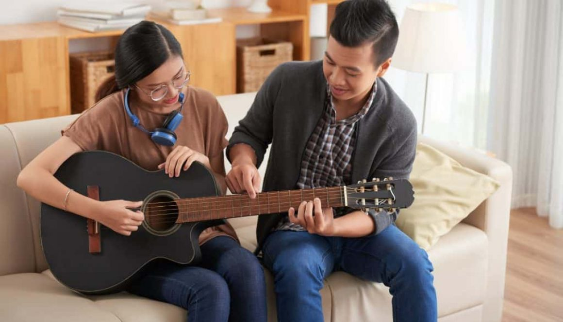 Couple learning to play guitar